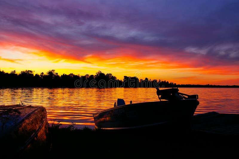 Coucher du soleil au-dessus de lac avec le bateau de pêche accouplé sur le rivage photographie stock