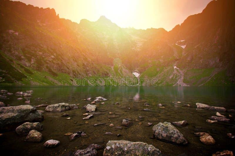 Coucher du soleil au-dessus de lac en montagnes image libre de droits