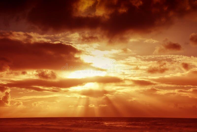 Coucher du soleil au-dessus de mer avec les nuages de tempête foncés image libre de droits