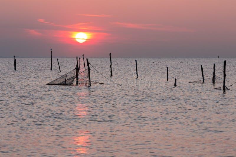 Coucher du soleil au-dessus de mer néerlandaise avec des filets de pêche images libres de droits