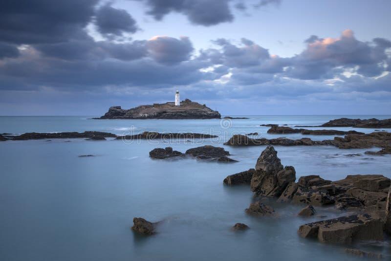 Coucher du soleil au-dessus de phare de Godrevy sur l'île de Godrevy dans St Ives Bay avec la plage et les roches dans le premier image libre de droits