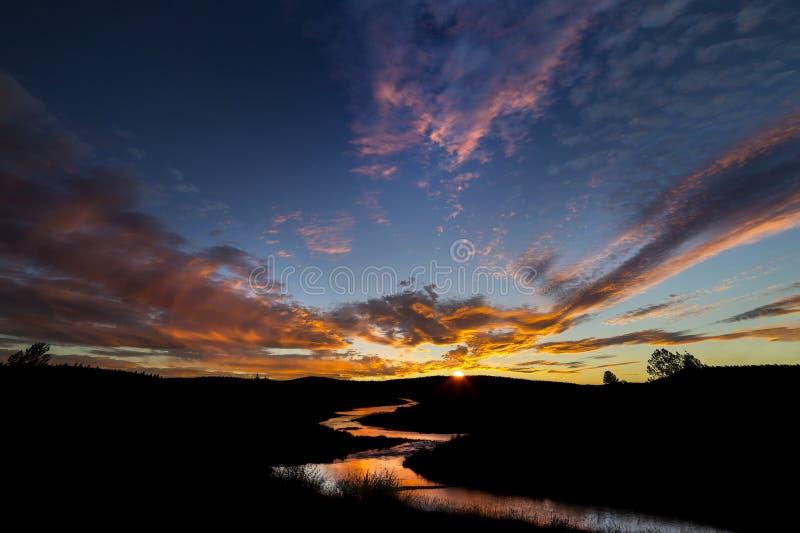 Coucher du soleil au-dessus de rivière d'enroulement photos stock