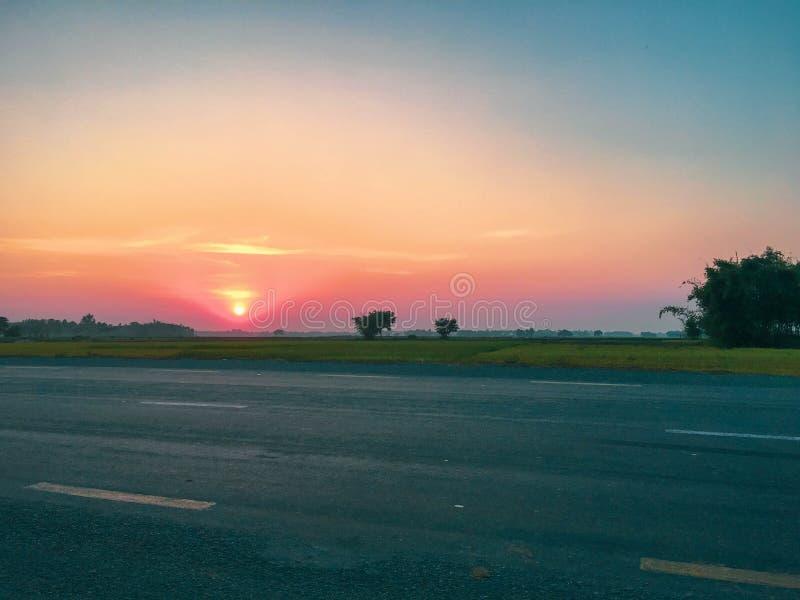 Coucher du soleil au-dessus de route dans le terai photos stock