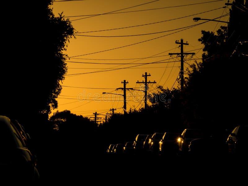 Coucher du soleil au-dessus de rue urbaine sombre avec des réflexions des voitures photo libre de droits