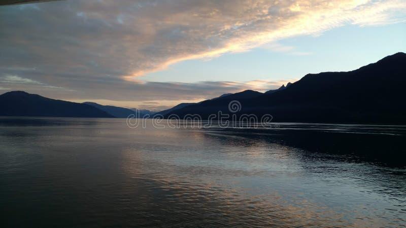 Coucher du soleil au-dessus des montagnes traversant la nébulosité lourde sur l'océan pacifique en Alaska Etats-Unis d'Amérique photos stock