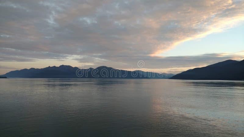 Coucher du soleil au-dessus des montagnes traversant la nébulosité lourde sur l'océan pacifique en Alaska Etats-Unis d'Amérique image libre de droits