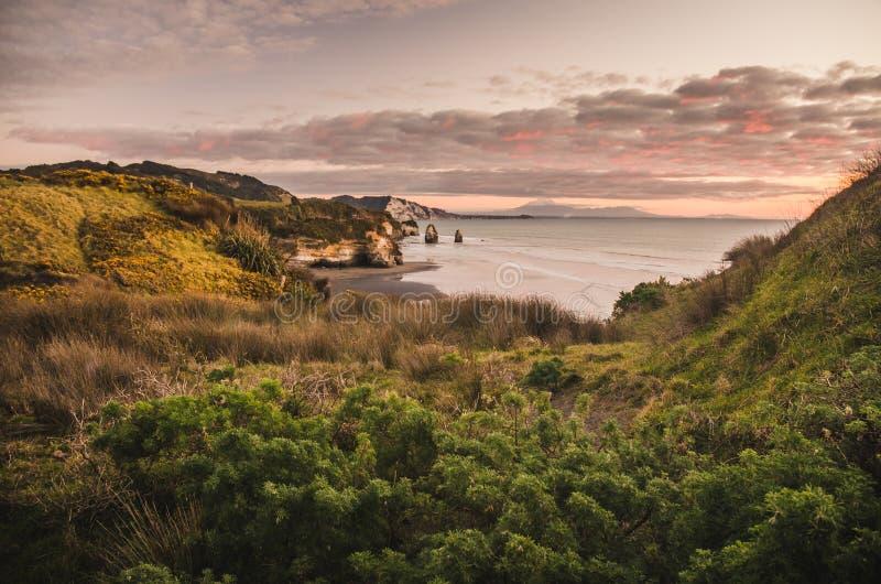 Coucher du soleil au-dessus des roches et du bâti Taranaki, Nouvelle-Zélande de bord de mer photos stock