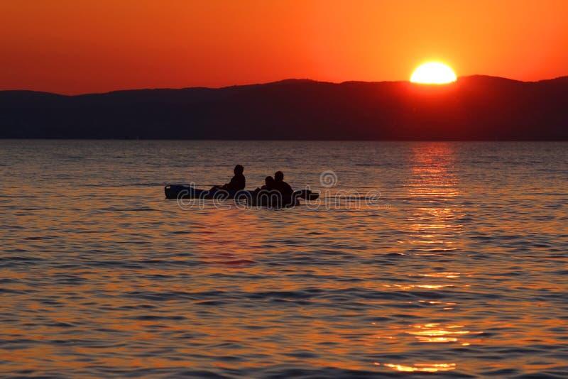 Coucher du soleil au-dessus du lac avec des bateaux images stock