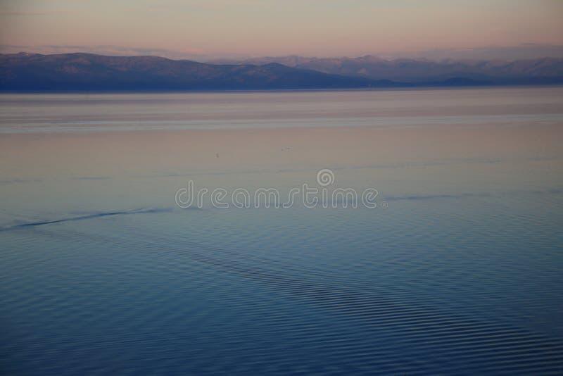 Coucher du soleil au-dessus du lac paisible Baikal avec des vagues image libre de droits
