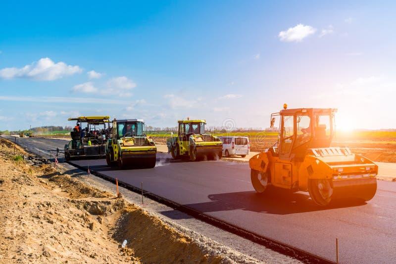 Coucher du soleil au-dessus du rouleau de route travaillant au chantier de construction photo libre de droits