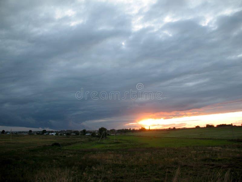 Coucher du soleil au-dessus du village image libre de droits