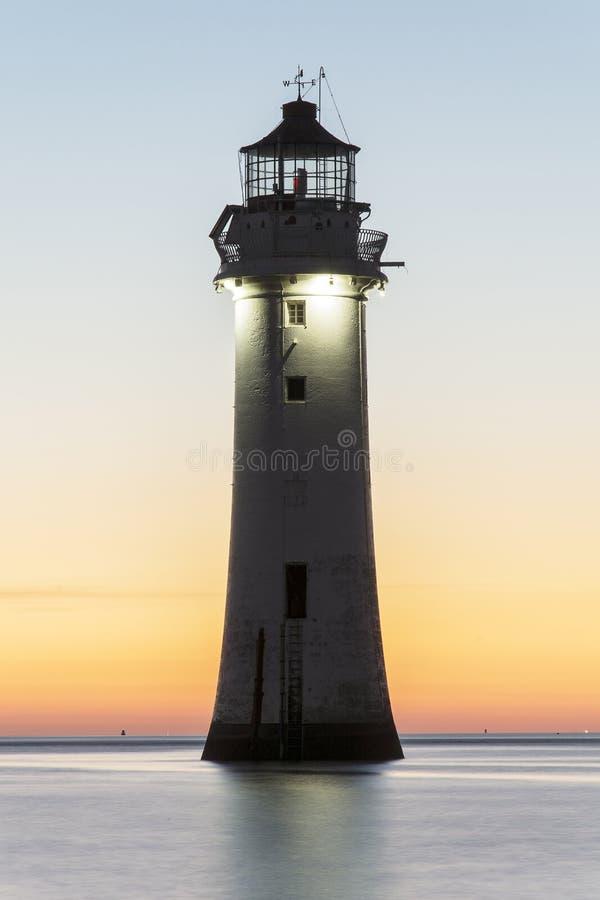 Coucher du soleil au phare nouveau Brighton de roche de perche photographie stock