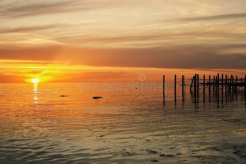 Coucher du soleil au rivage de la ville de désert avec les ruines et les restes du vieux dock image stock