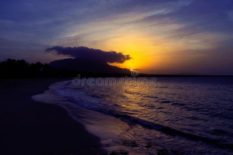 Coucher du soleil aux nuances jaunes et pourpres avec une réflexion en mer, images libres de droits