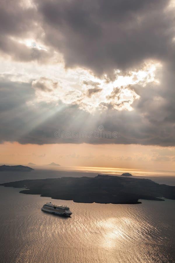Coucher du soleil avec des rayons de soleil au-dessus de volcan avec le bateau sur l'île de Santorini en Grèce images libres de droits