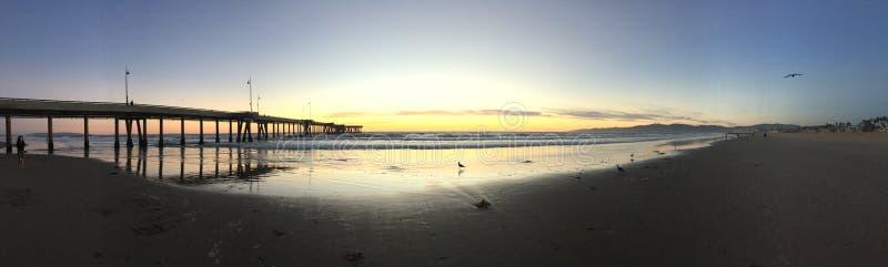 Coucher du soleil avec des seaguls silhouettés au pilier images stock