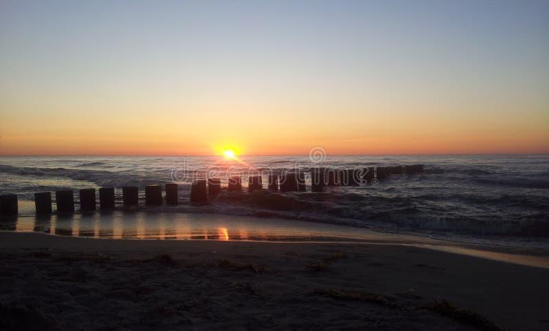 Coucher du soleil avec le brise-lames par la mer baltique photo stock