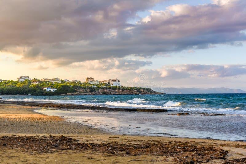 Coucher du soleil avec le ciel dramatique au-dessus de la plage chez Rafina, Grèce images stock