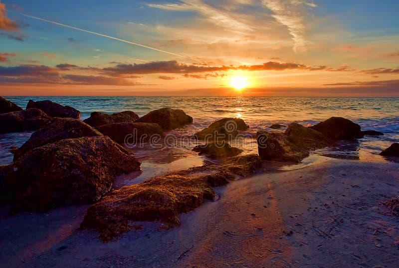 Coucher du soleil avec le rayon de soleil au-dessus de Rocky Seashore photos libres de droits