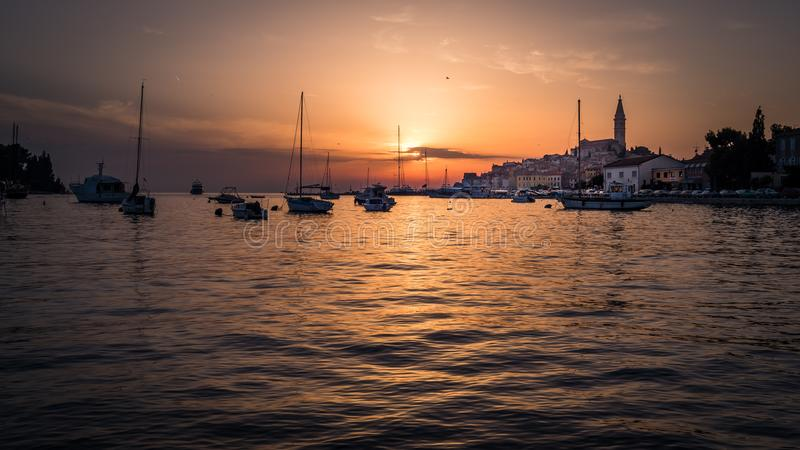Coucher du soleil avec les bateaux et la vieille ville de Rovinj en Croatie photos stock