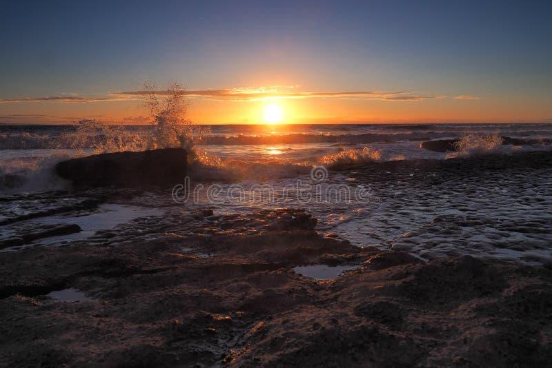 Coucher du soleil avec les nuages et le jet oranges des vagues se brisant sur des roches à la baie de Dunraven, Vale de Glamorgan photo libre de droits