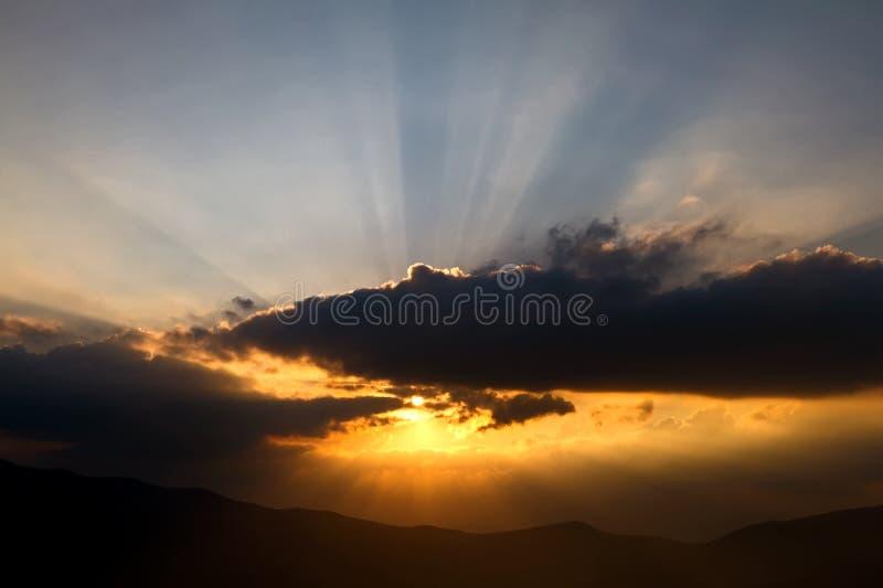 Coucher du soleil avec les rayons de soleil au-dessus du nuage image libre de droits