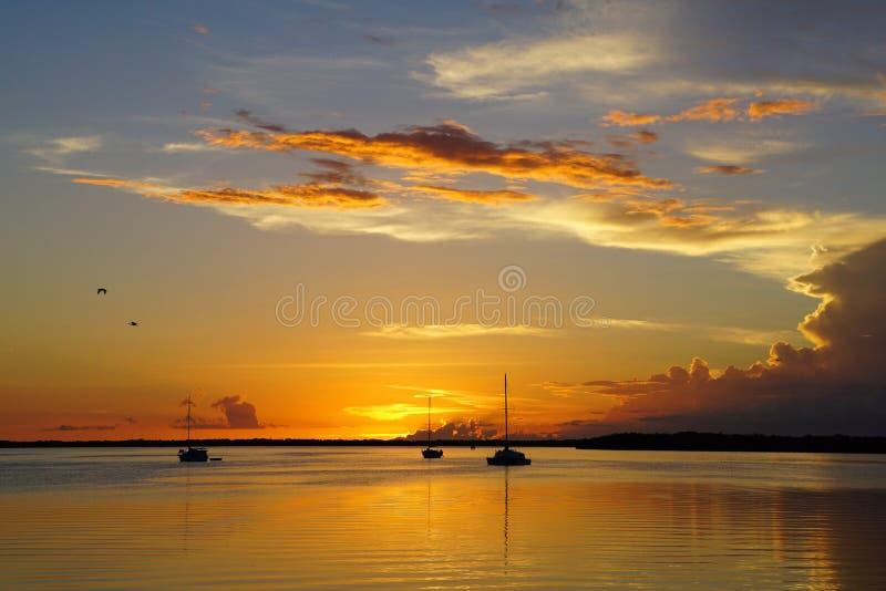 Coucher du soleil avec trois voiliers ancrés dans l'océan photographie stock libre de droits