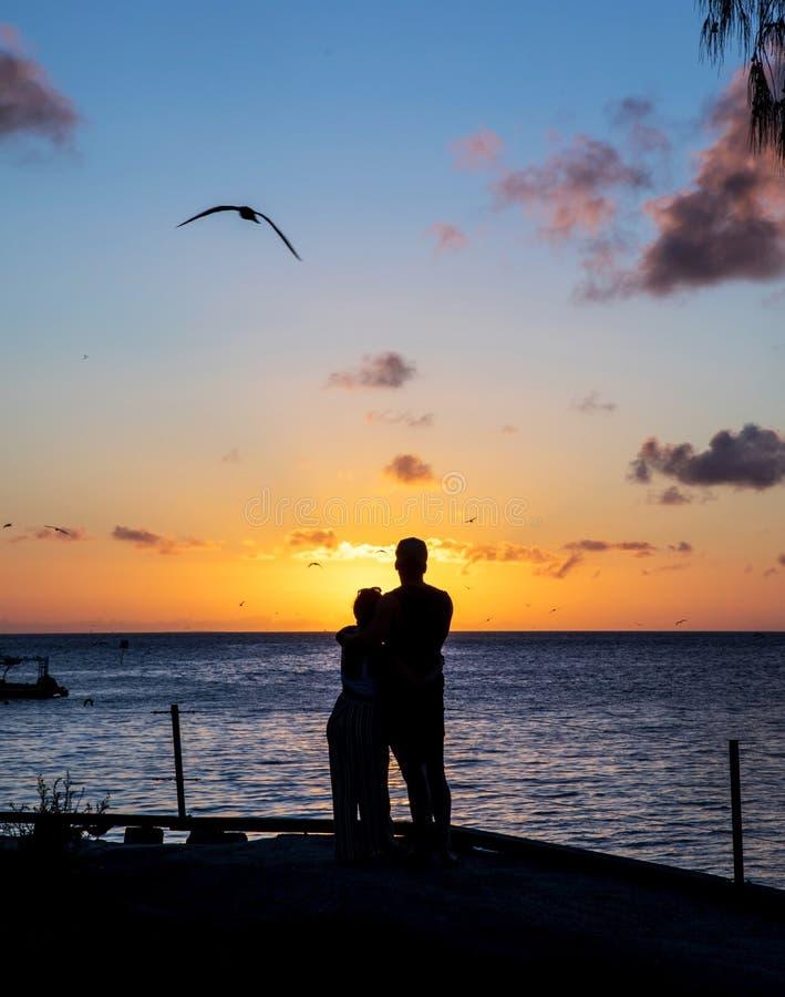 Coucher du soleil avec un jeune couple affectueux en silhouettes images stock