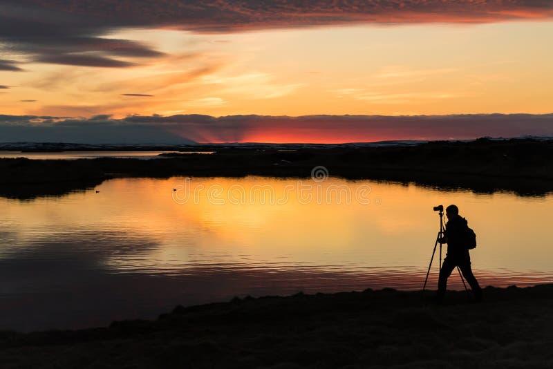 Coucher du soleil avec une silhouette d'un cameraman chez Myvatn Islande image stock