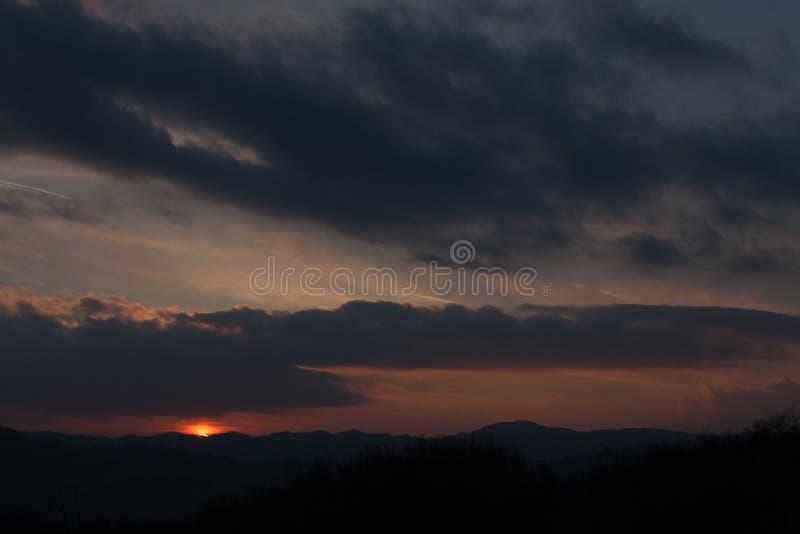 Coucher du soleil behing la colline lointaine image stock