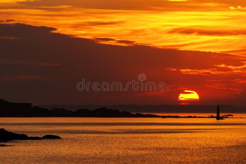 Coucher du soleil brûlant au-dessus de la mer avec un phare image stock