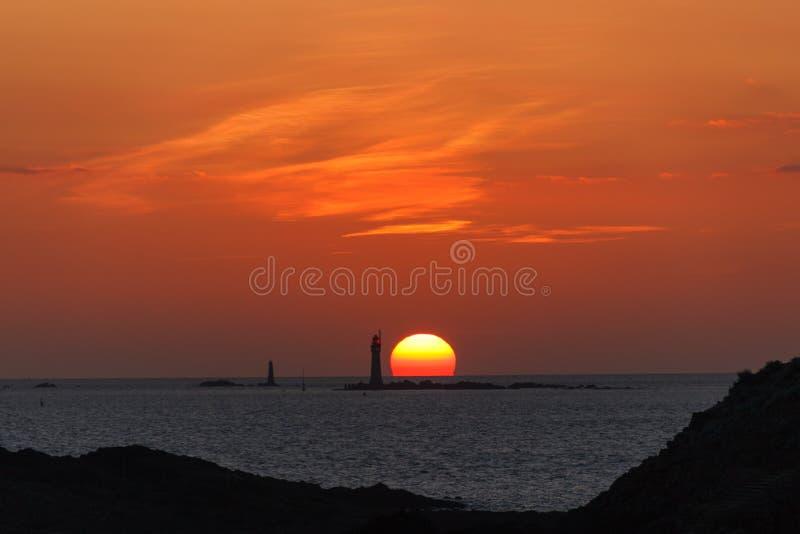 Coucher du soleil brûlant dans l'océan avec un phare images stock