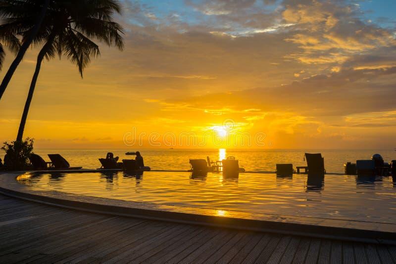 Coucher du soleil, chaises de plage, palmiers, silhoue de piscine d'infini photographie stock