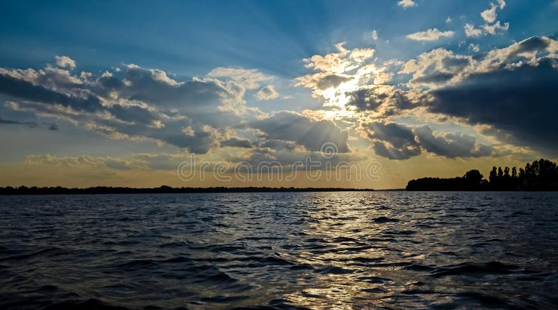 Coucher du soleil chaud d'été au-dessus de la rivière Danube sur le fond d'un ciel bleu photos libres de droits