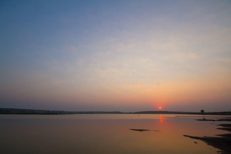 Coucher du soleil coloré près de lac et de collines photo libre de droits