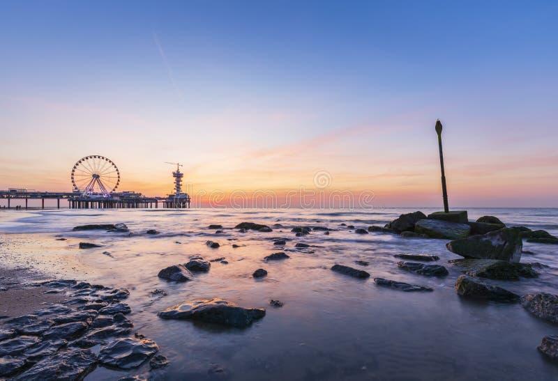 Coucher du soleil coloré sur le littoral, la plage, le pilier et la roue de ferris, Scheveningen, la Haye photos stock