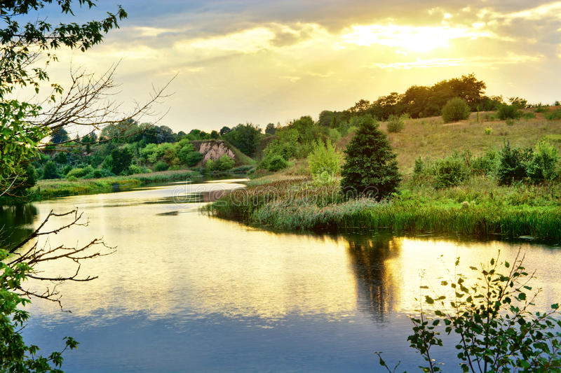 Coucher du soleil d'été par la rivière avec des réflexions d'or image libre de droits