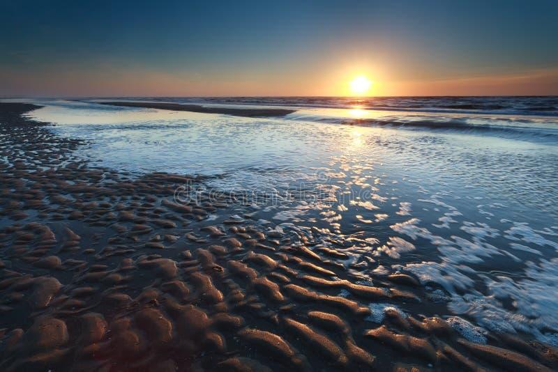 Coucher du soleil d'or au-dessus de la plage du nord de sable de mer à marée basse image libre de droits