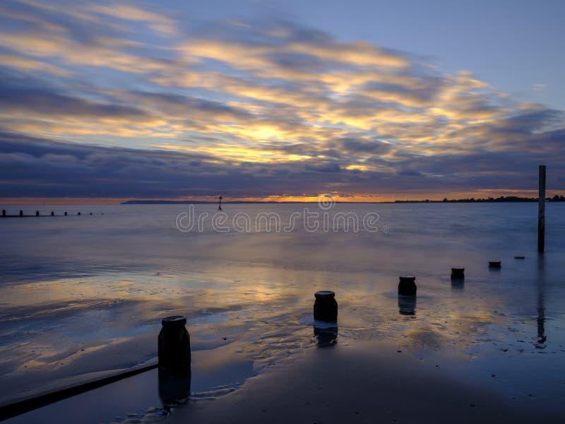 Coucher du soleil d'automne au-dessus du Solent de la plage occidentale de Wittering, le Sussex occidental LE R-U photos stock