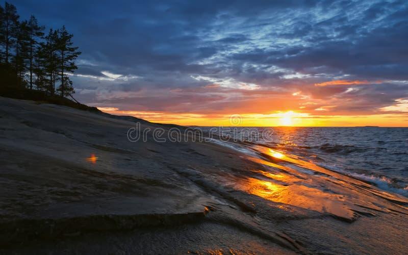 Coucher du soleil d'or en ciel orageux au-dessus du lac Onega images stock