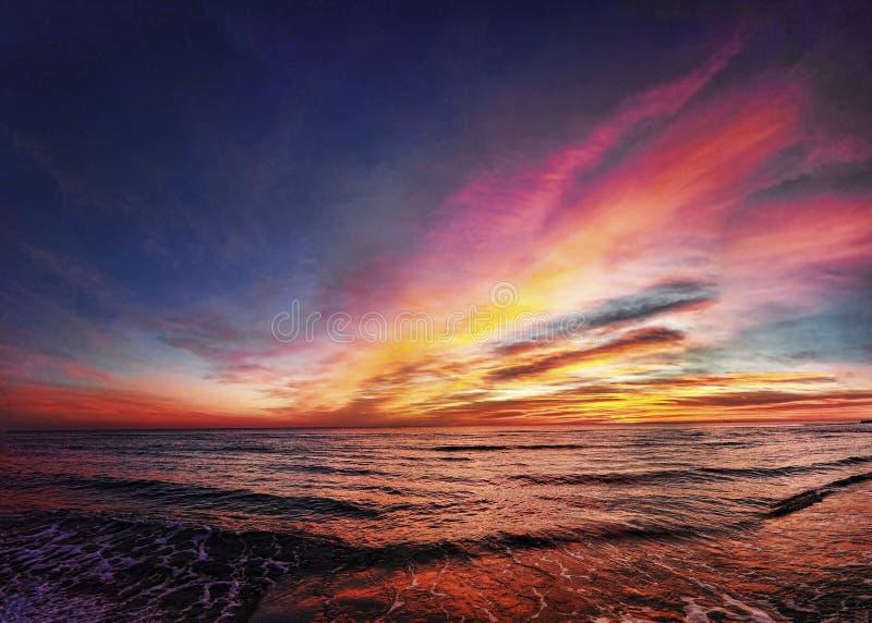 Coucher du soleil d'or impressionnant d'heure au-dessus de la plage avec le ciel coloré en pastel merveilleux images stock