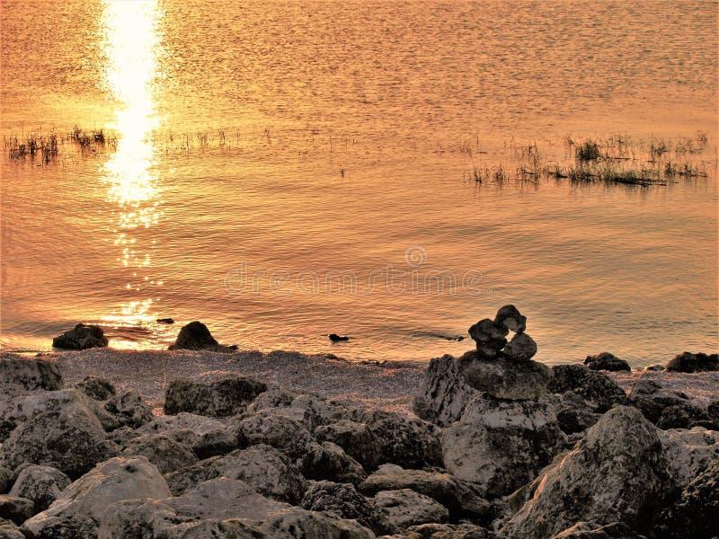 Coucher du soleil d'Okeechobee de lac et cairn de roche photo stock