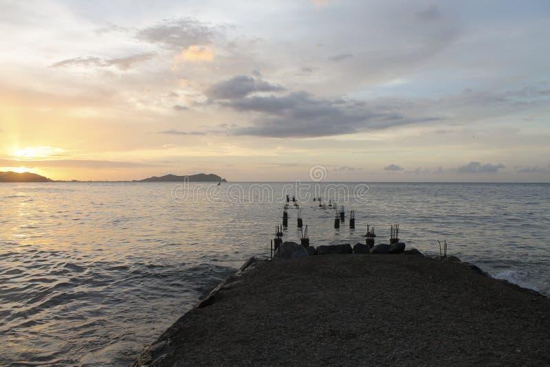 Coucher du soleil d'un pilier sur la plage photo libre de droits