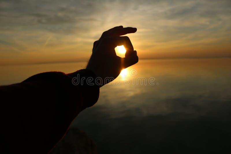 Coucher du soleil dans ma main photo stock