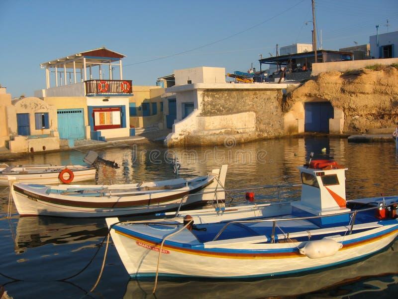 Coucher du soleil dans un petit port de pêche et des ses bateaux d'île de Milos en Grèce photos stock