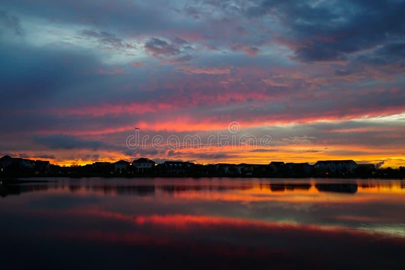 Coucher du soleil dans un voisinage qui réfléchit sur un lac photo libre de droits