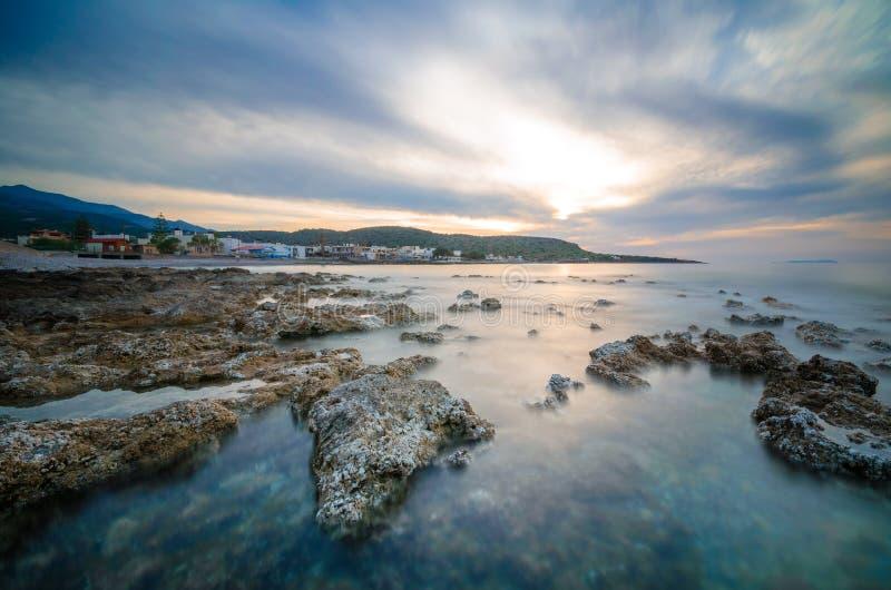 Coucher du soleil de Gorgeus au-dessus de mer avec des vagues, des roches et le village grec traditionnel de Milatos, Crète image stock