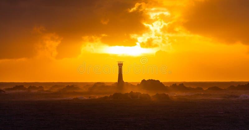 Coucher du soleil de Guernesey derrière le phare de Hanois image libre de droits