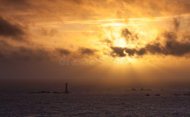 Coucher du soleil de Guernesey derrière le phare de Hanois photos stock