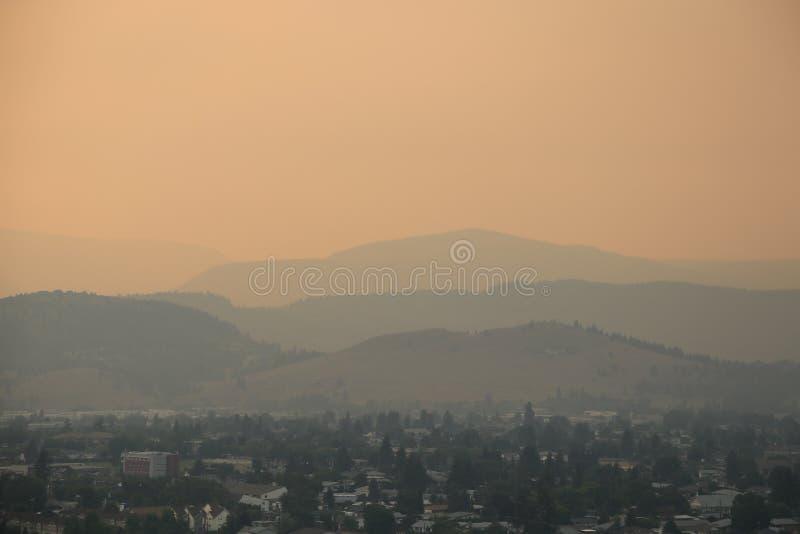 Coucher du soleil de Kelowna- de saison du feu avec le ciel fumeux 4 couches de représentation de montagnes photos stock